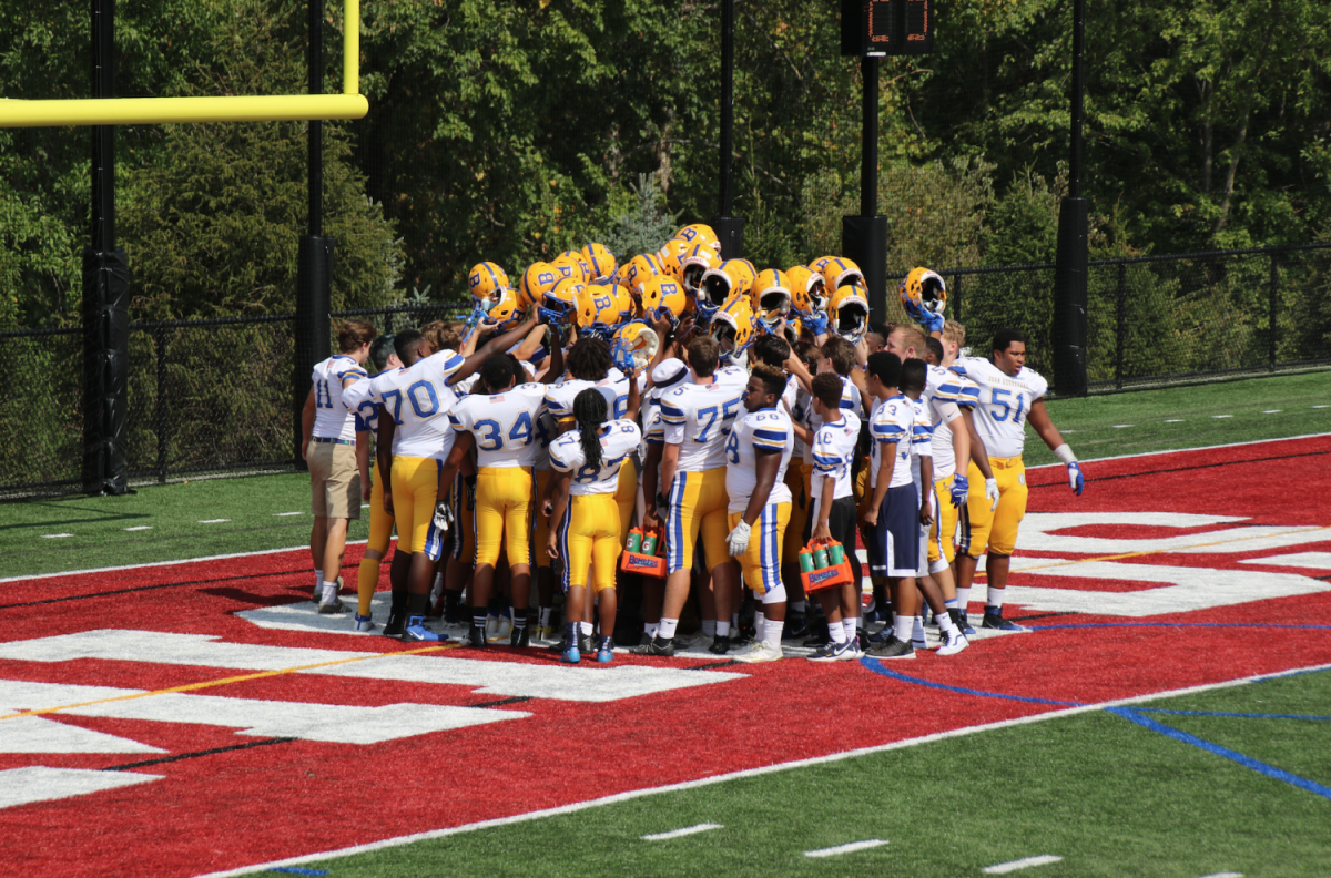 JBS football team huddles before kickoff in the game.
