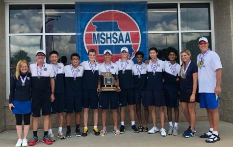 The team celebrates and poses with their state championship trophy.